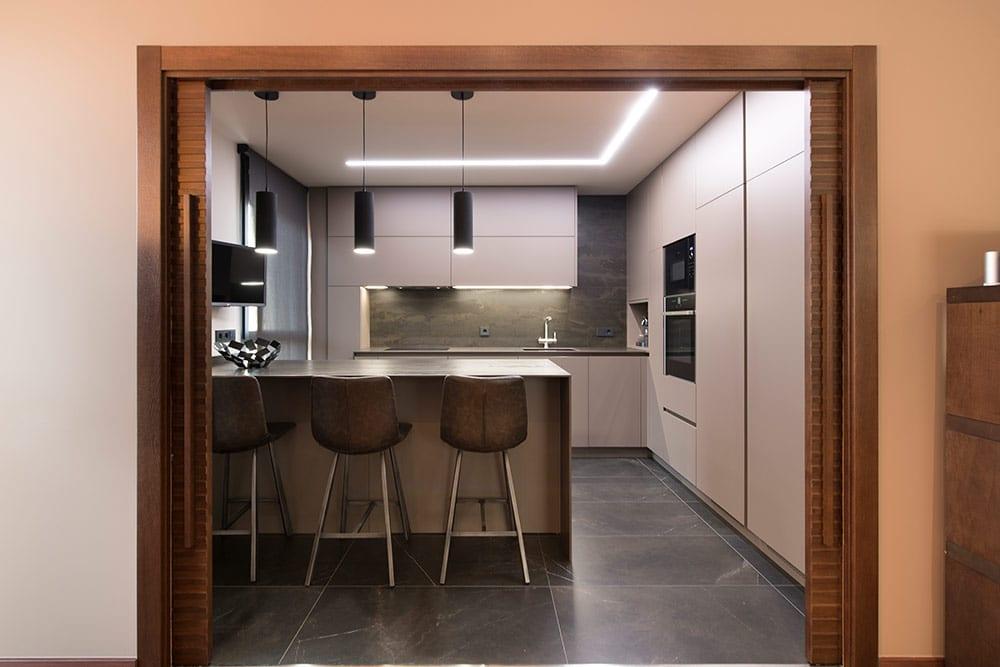 Hueco muro cocina semi abierta al salón por puerta corredera de madera