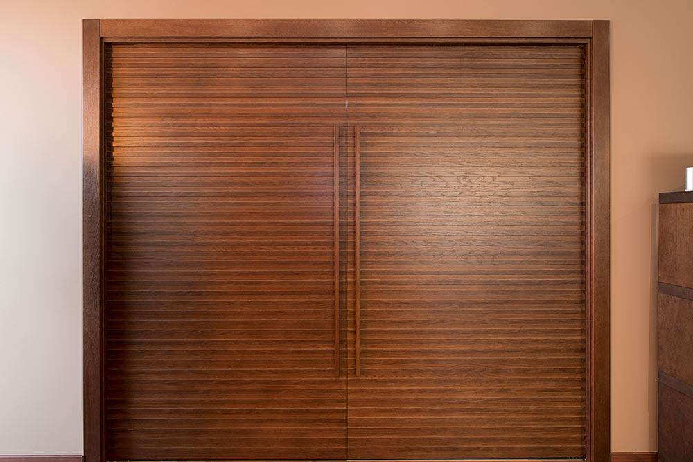 Puerta corredera madera de dos hojas que separa la cocina del salón