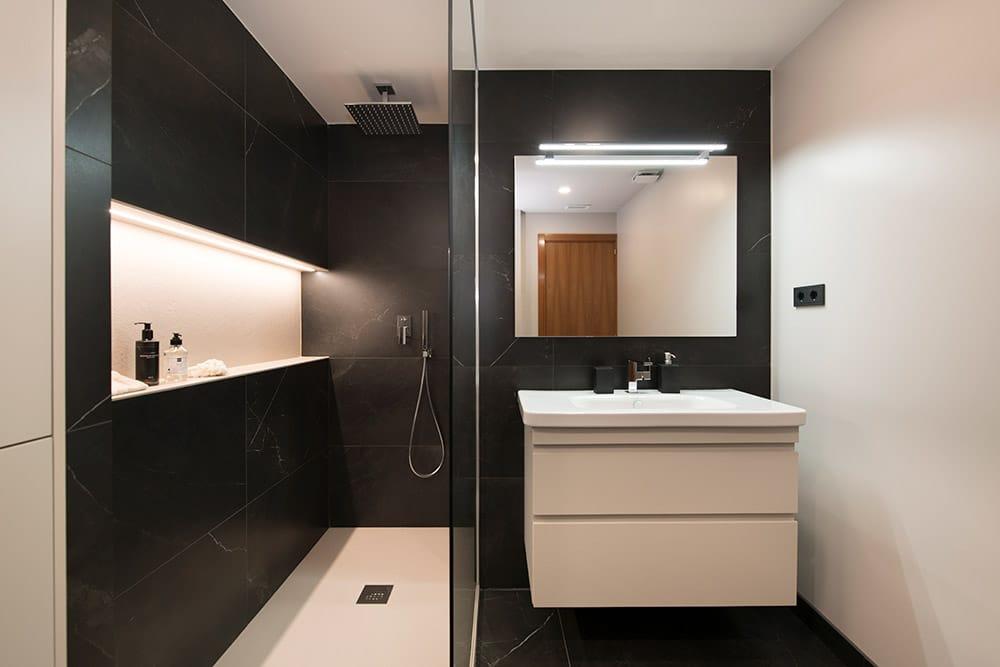 Zona de lavabo y ducha con contraste blanco y negro