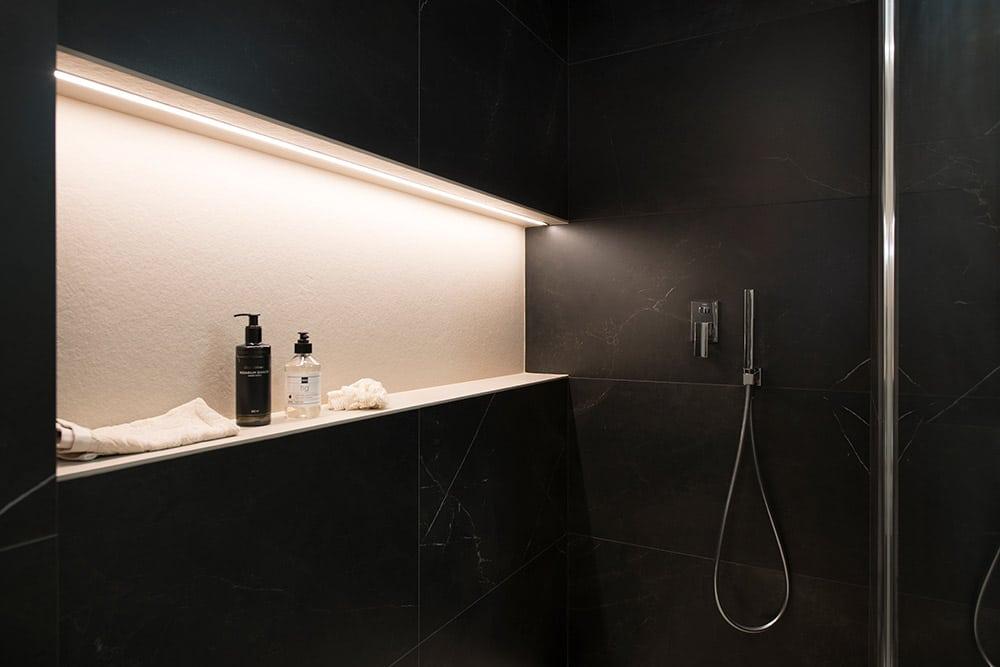 Hornacina ducha en blanco en un baño de baldosas negras