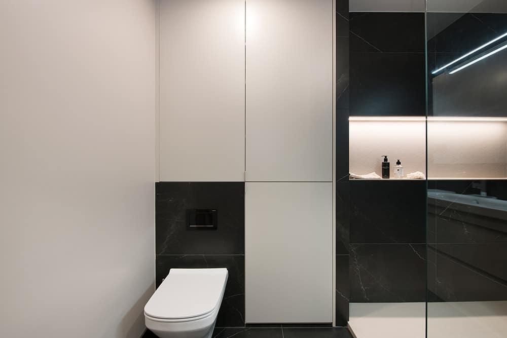 Zona del inodoro con muebles y revestimientos en blanco y negro