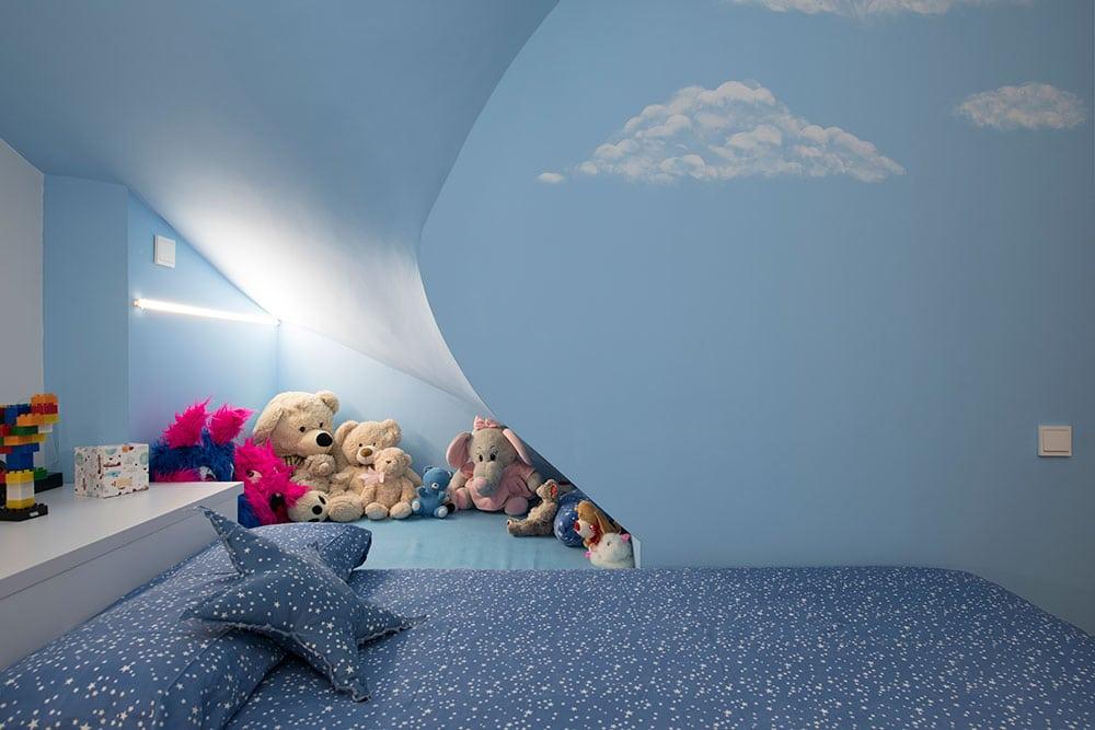 Hueco bajo escalera para guardar juguetes en habitación infantil