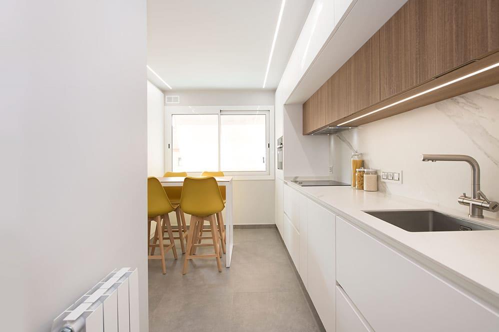 Cocina enmarcada de color blanco y madera. cocina con barra para comidas