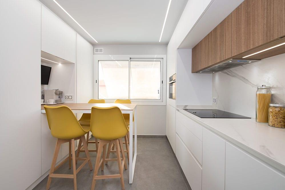 Cocina blanca con mesa de barra con taburetes - Sincro