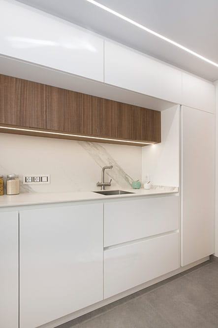 Cocina enmarcada en color. Encimera mármol blanco y mueble superior de madera