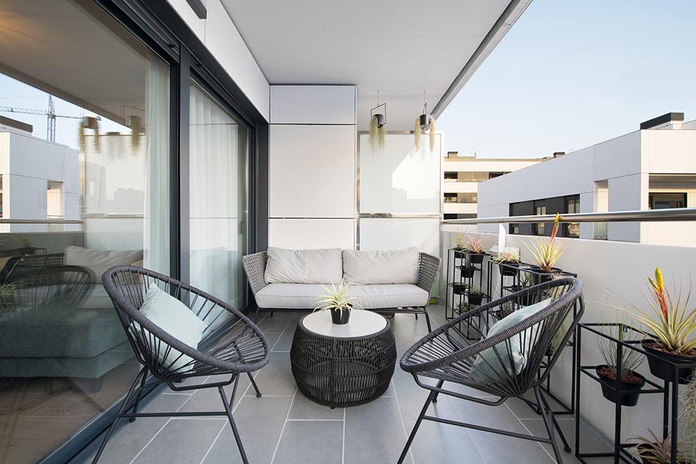 Terraza con sofá, mesa y silla kave Home