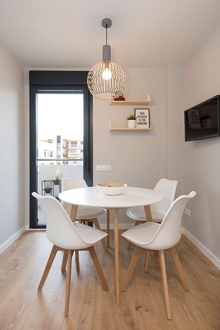 comedor en cocina estilo nórdico. Mobiliario blanco y madera.