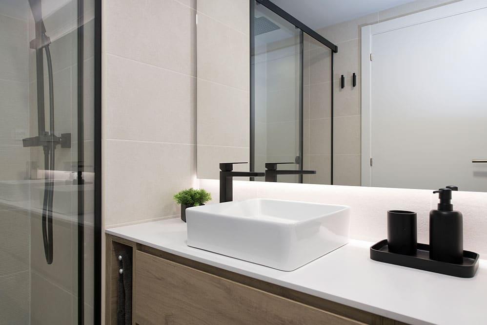 Detalle lavabo blanco sobre mueble baño i grifería negra
