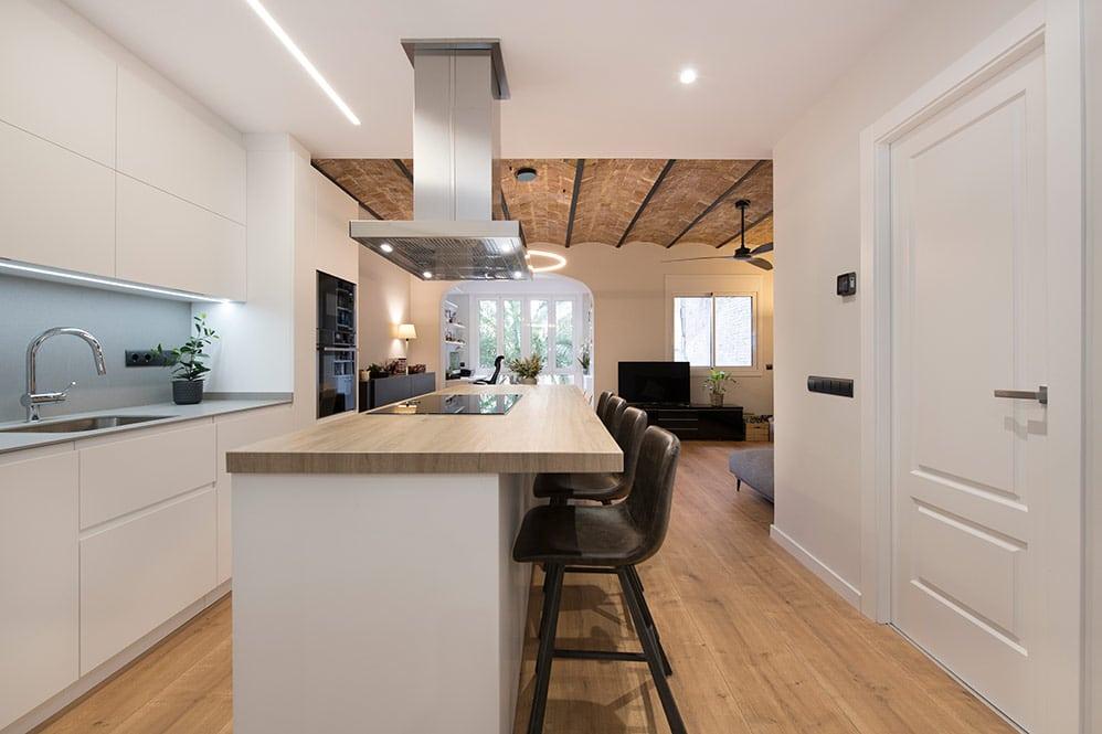 Isla de cocina con campana extractora y barra con taburetes