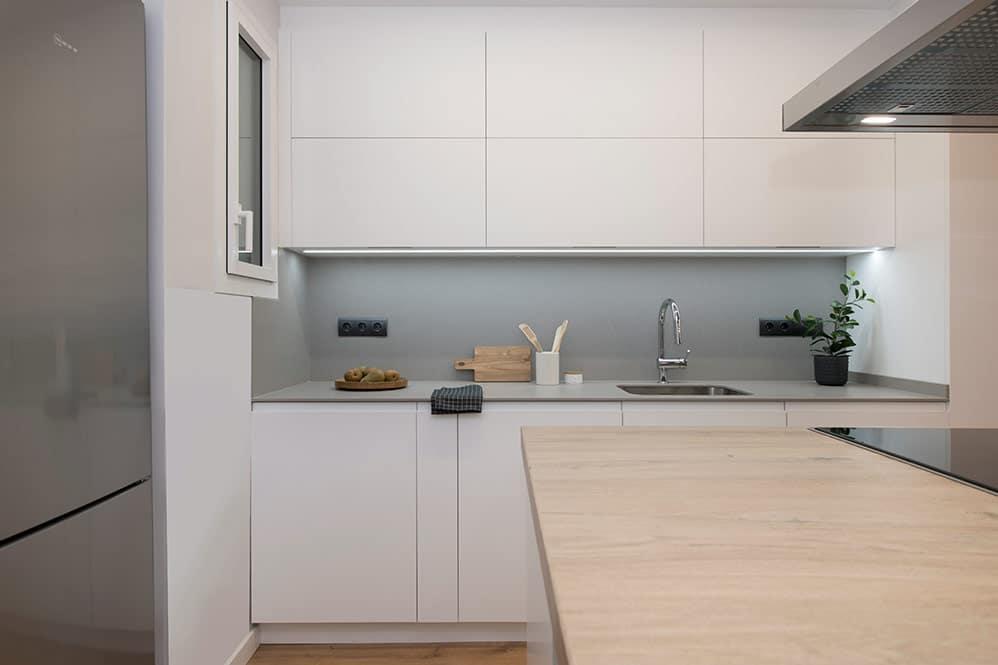Salpicadero de cocina mueble alto y bajo blanco. Encimera gris.