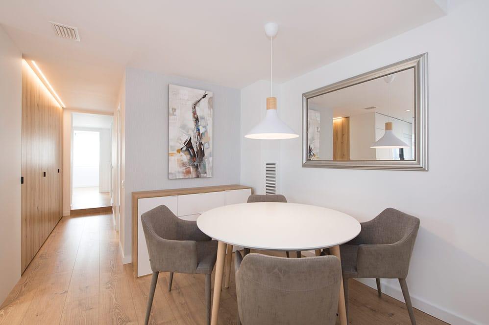 Comedor con mesa redonda blanca y sillas grises. De estilo escandinavo