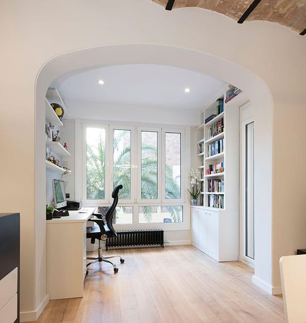 Despacho integrado al salón con gran ventanal y arco.