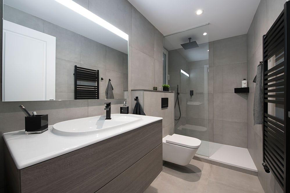 Baño con ducha con tonalidades grises y toques negro.
