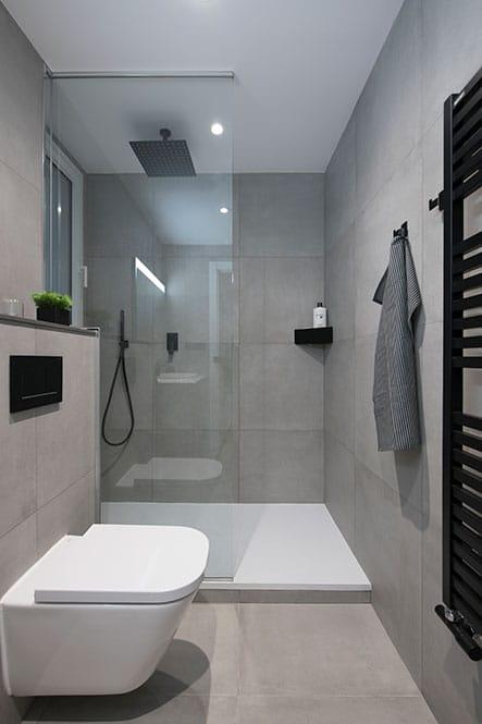 Baño con ducha con revestimientos porcelánicos de color gris y accesorios de color negro