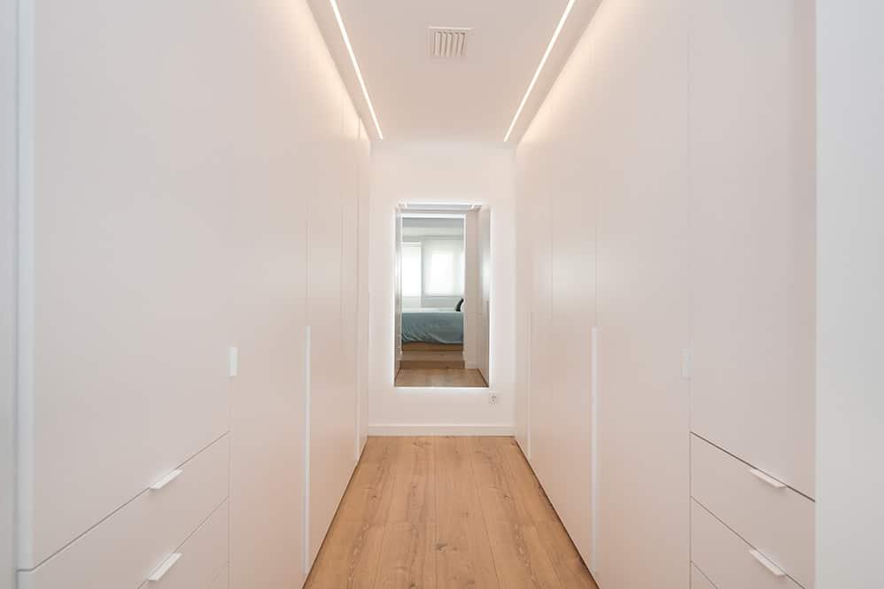 Armarios en paralelo en vestidor con espejo retroiluminado en el muro del fondo