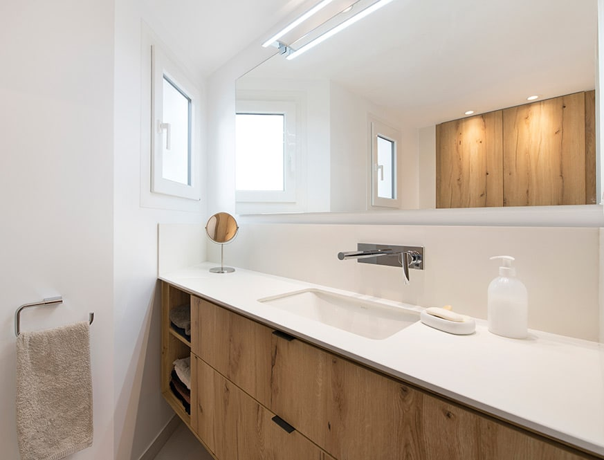 Mueble de baño en una esquina con acabado de madera
