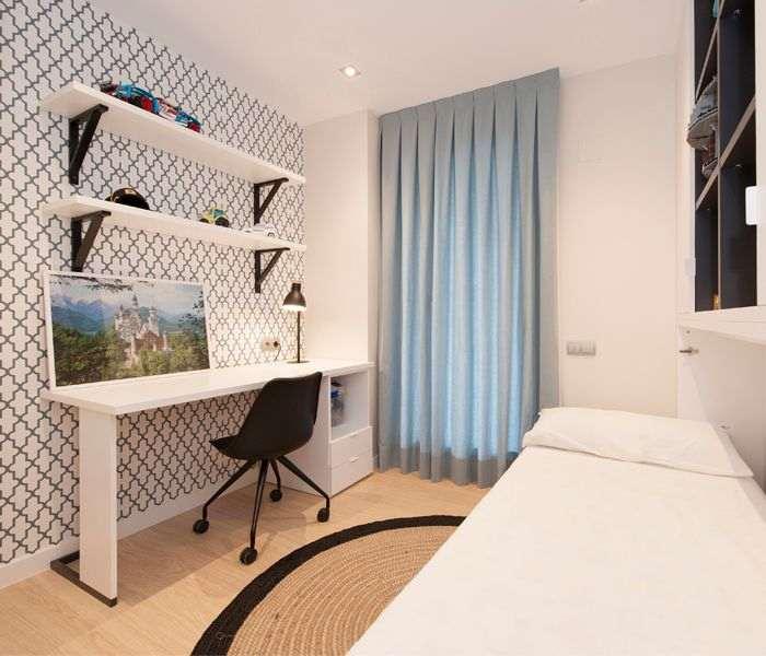 Habitación juvenil chico con papel pintado y mobiliario: escritorio, silla, mueble cama abatible.
