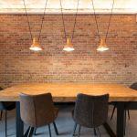 Menjador estil decoratiu industrial amb fusta massissa, potes de ferro, llums color mostassa i paret maó vist.