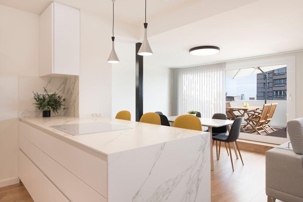 Península de cocina con vitro color blanco y barra con taburetes para comer. Lámparas colgantes de color gris.