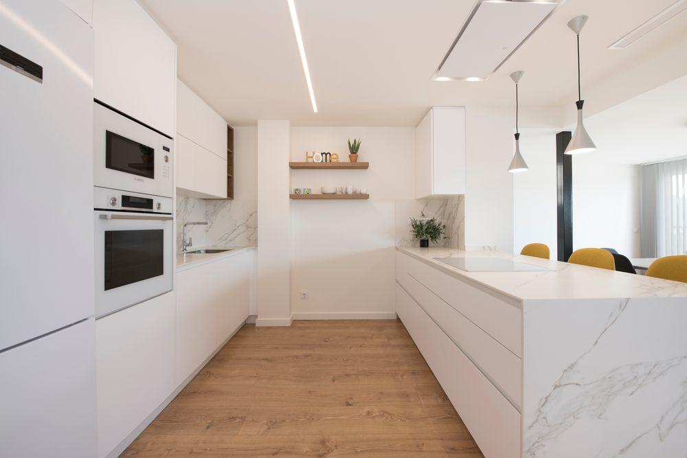 Zona de cocción y limpieza cocina con península. Reforma cocina en un ático de Barcelona. Sincro