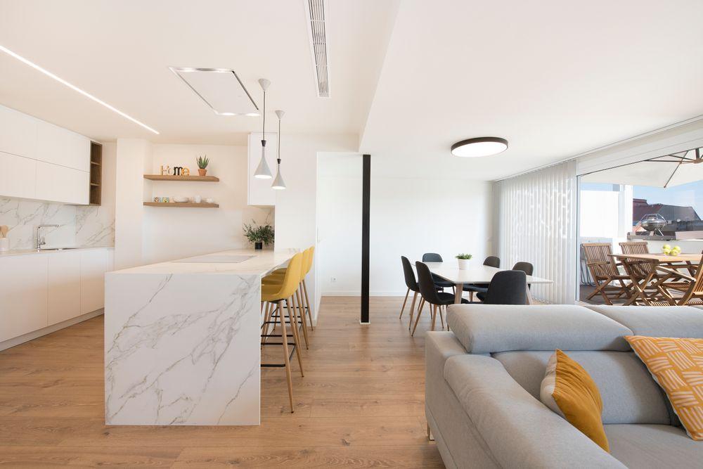 Zona de día abierta que alberga cocina, comedor y salón. Reforma ático Sincro en Barcelona