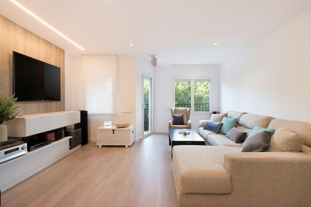 Salón con panel de madera y televisor colgado. Reforma en Hospitalet de Llobregat