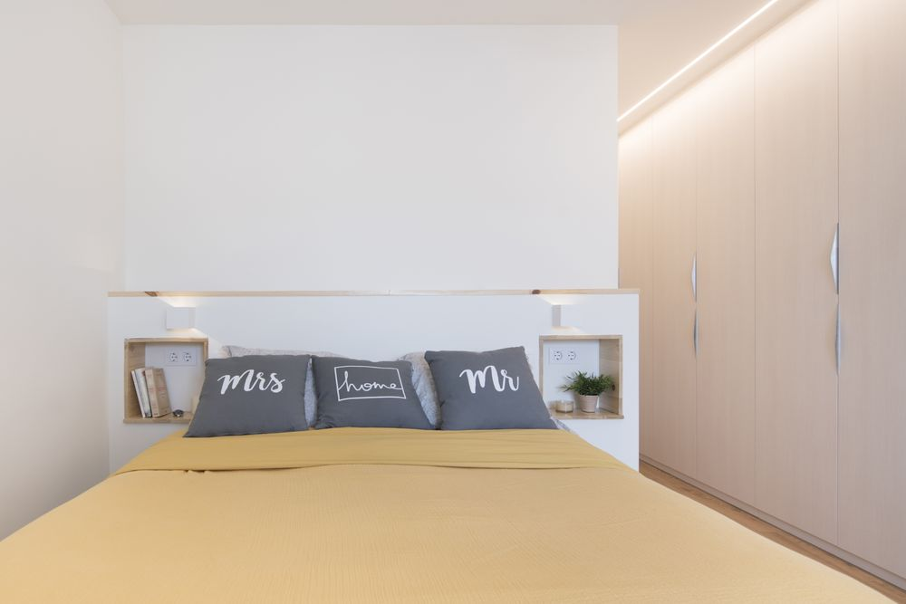 Cabecero de cama con dos huecos integrados como mesilla de noche. Sincro