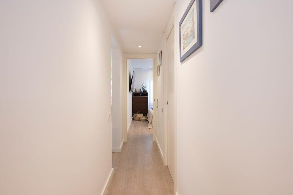 Pasillo reformado con paredes blancas y parquet