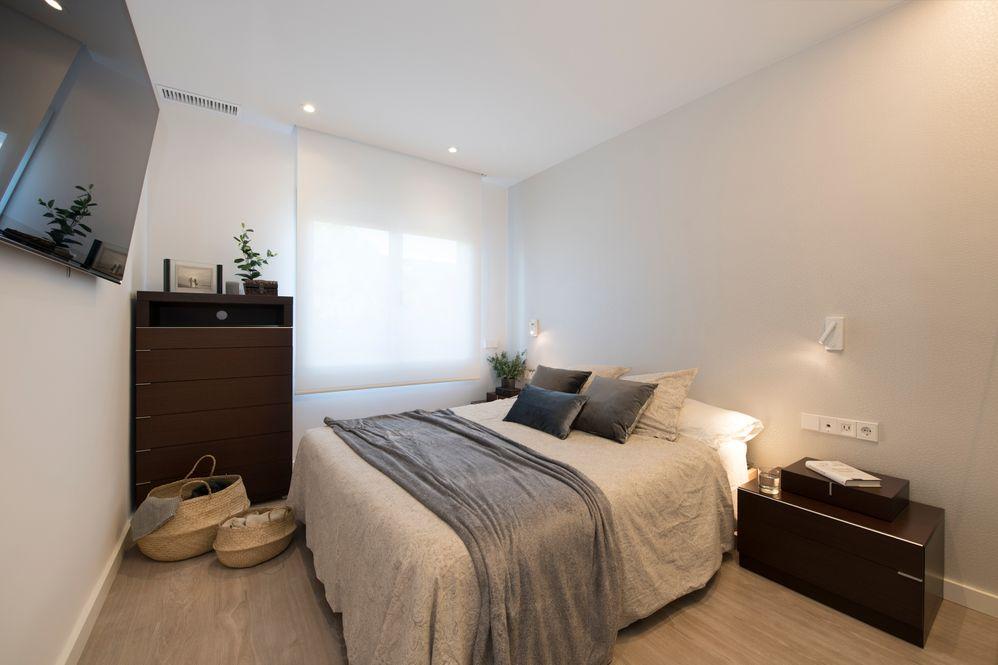 Dormitorio con tv colgada en la pared