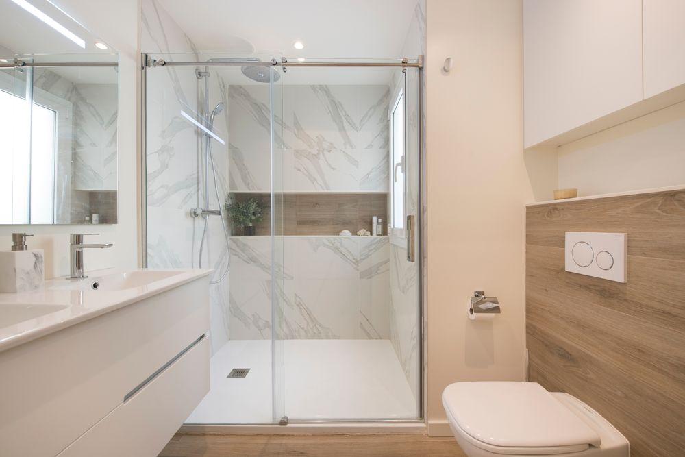 Cuarto de baño en suite con ducha que combina baldosa imitación madera y mármol blanco con vetas grises. Sincro reformas Barcelona