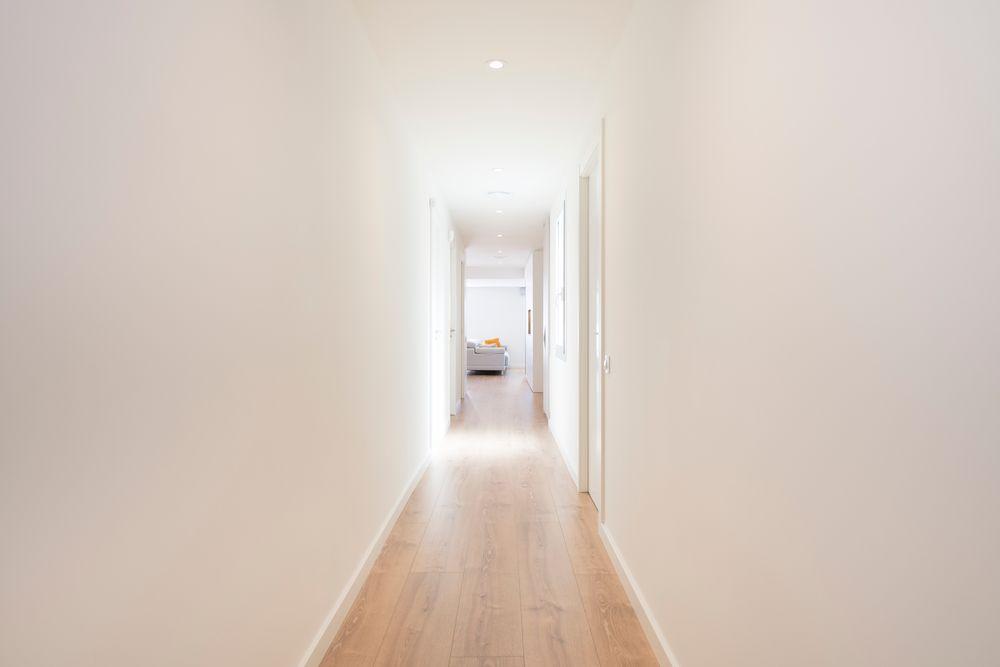 Pasillo con parquet roble y paredes blancas
