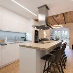 Foto portada blog islas de cocina. Con vitro y campana decorativa techo. Barra taburetes