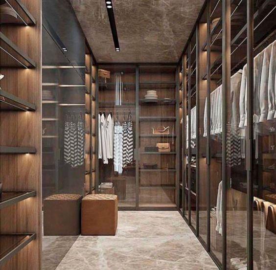 Vestidor sobri i elegant en forma d'U. Colors foscos i armaris amb portes de vidre.