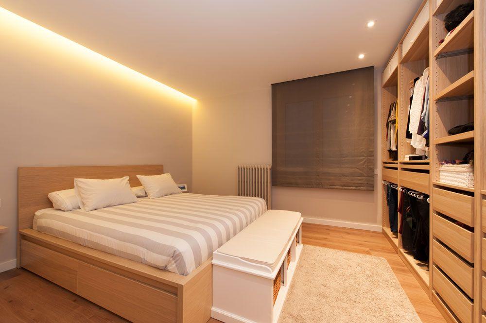 Vestidor de dormitori amb un armari obert al llarg de la paret de davant del llit. Amb banc i catifa. Projecte Sincro a Barcelona.
