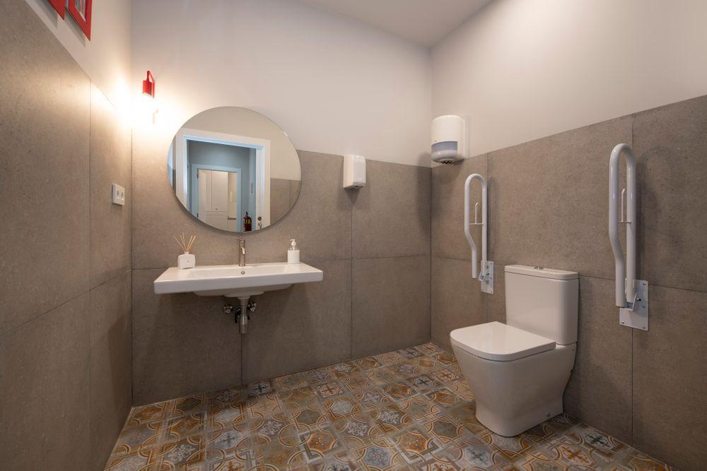 Baño con baldosas imitación hidráulicos de colores del centro médico reformado por Sincro.