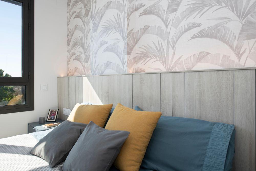 Cabecero de cama diseñado con panel de madera y papel pintado motivo plantas tropicales