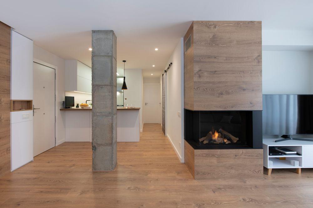 Salón diafano con chimenea de gas con estructura de madera roble claro