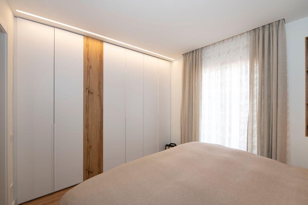 Armario a medida en toda la pared del dormitorio. Con acabado color blanco y un poco de madera