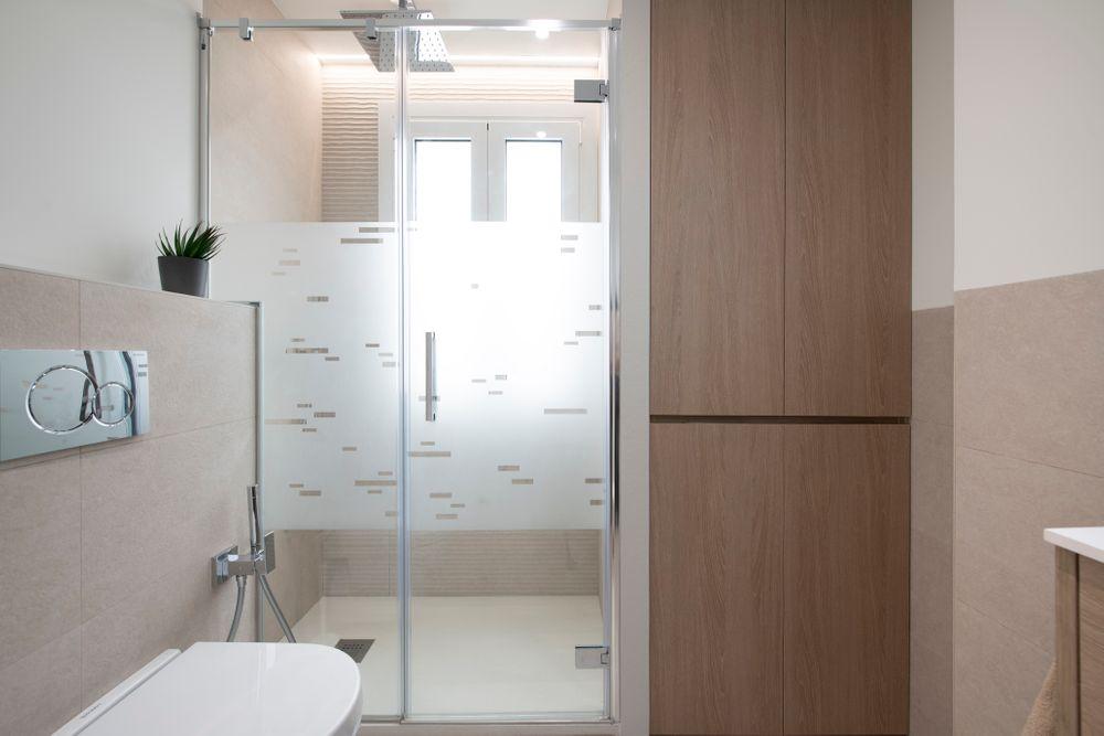 Mampara de ducha recortada para el murete del inodoro